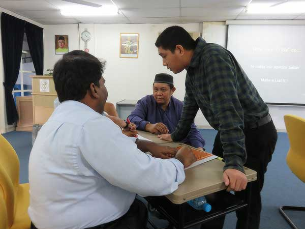 Nadhir (standing) conducts a Disability Equality Training session with participants.